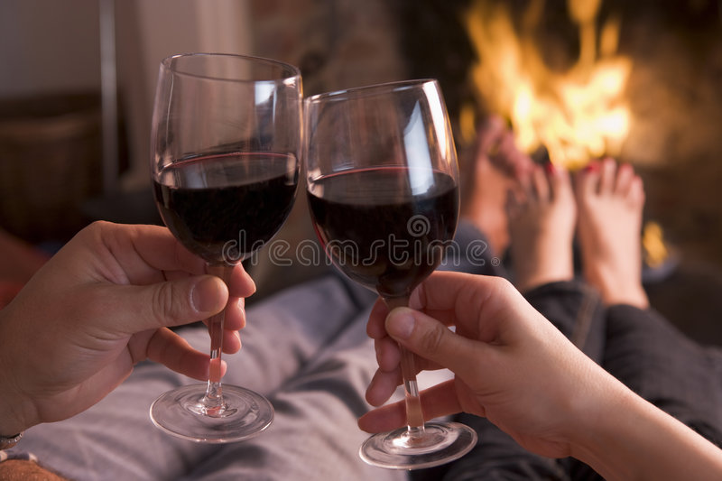 Feet warming at fireplace with hands holding wine royalty free stock photo