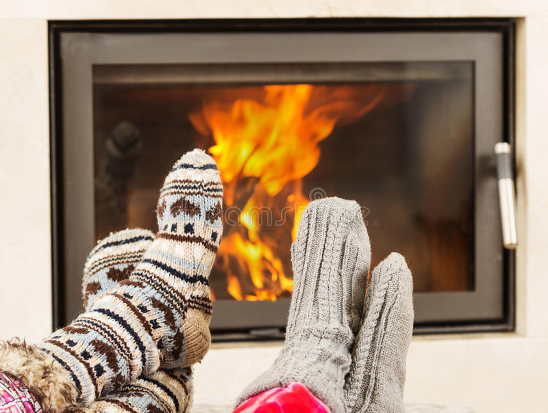 Feet warming by fireplace. Feet in wool socks warming at the fireplace royalty free stock photography
