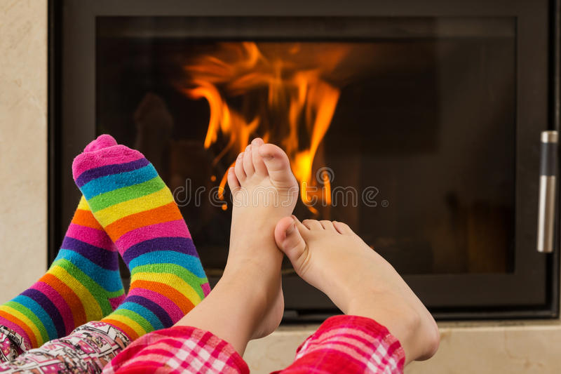 Feet warming by fireplace. Feet in wool socks warming at the fireplace royalty free stock photo