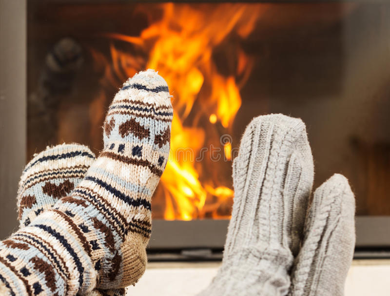 Feet warming by fireplace. Feet in wool socks warming at the fireplace stock photography