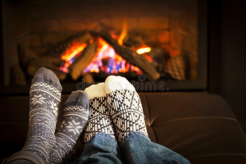 Feet warming by fireplace. Feet in wool socks warming by cozy fire stock photo
