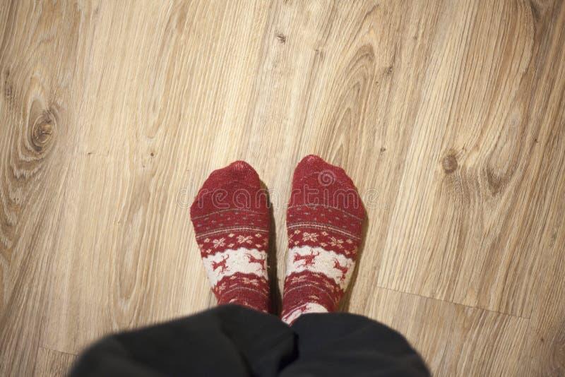 Feet wearing Christmas socks on wood floor. Happy family at home. Xmas holidays concept. Feet wearing Christmas socks on wood floor. Happy family at home royalty free stock photo