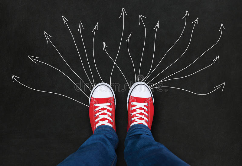 Feet wearing red shoes on black background royalty free stock photography