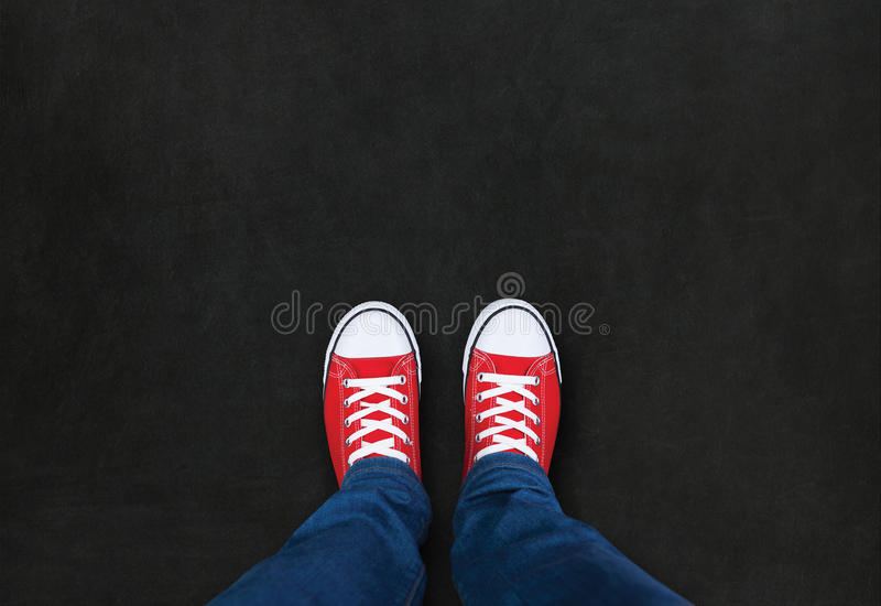Feet wearing red shoes on black background. With space for text royalty free stock image