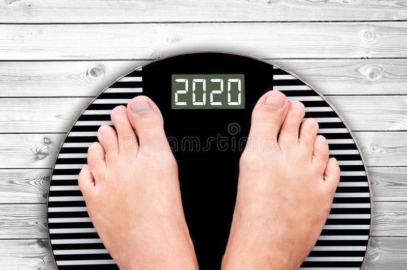 2020 feet on a weight scale on white planks, new year holiday food nutrition and diet concept. 2020 feet on a weight scale on white planks, new year and holiday royalty free stock photo