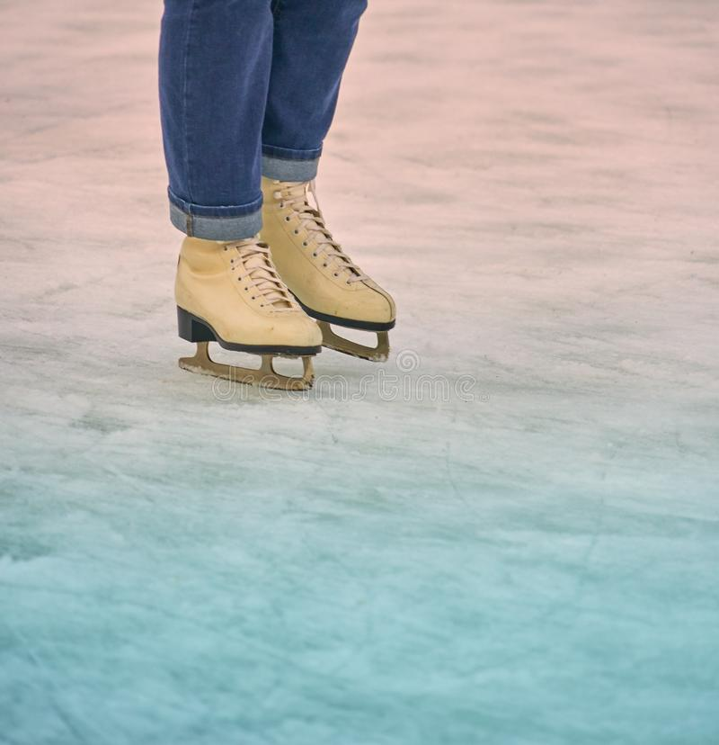 Feet with white skates and legs with the lower part of blue jeans on white ice with blue and red gleam.  royalty free stock photography