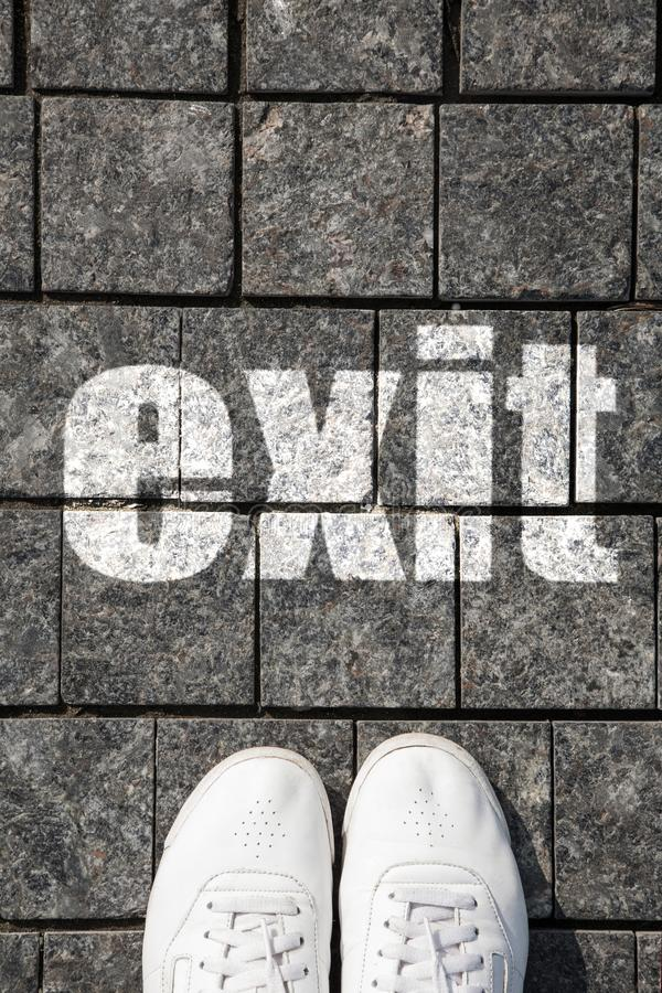 Foot in the white sneakers on the cobblestone paving in front of the EXIT, top view. Concept of a way out of a difficult situation stock photos