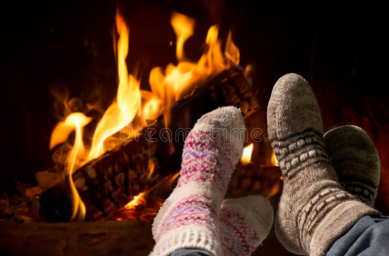 Feet in wool socks warming at the fireplace. Couple relaxing at the fireplace on winter evening stock images
