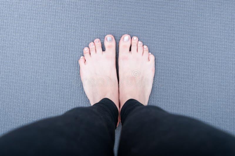 Feet on yoga mat. In detail mode stock image