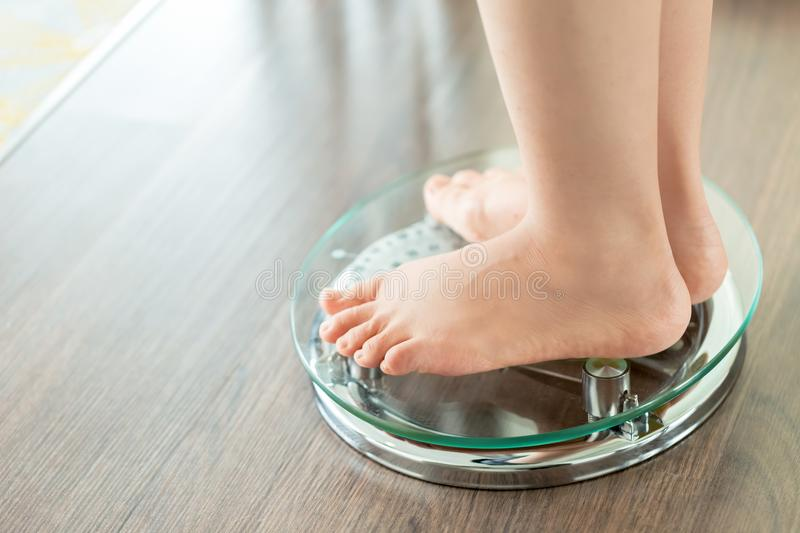 Feet of a young woman measuring her weight on a scale royalty free stock photos