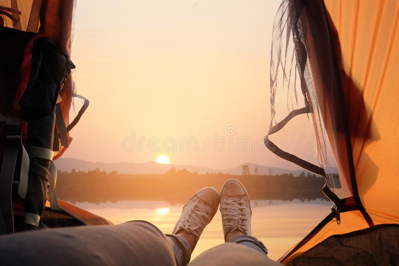 Feet of young women relaxing with lake view from tent camping entrance outdoor. Travel wanderlust lifestyle concept. Adventure vacations outdoor, Summer holiday stock images