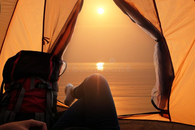 Feet of young women relaxing with lake view from tent camping entrance outdoor. Travel wanderlust lifestyle concept. Adventure vacations outdoor, Summer holiday royalty free stock photo