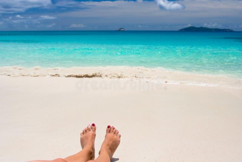 Feets na praia branca imagem de stock