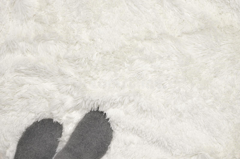 Feets on shaggy carpet. Woman feet in warm socks on white shaggy carpet. Top view royalty free stock photos