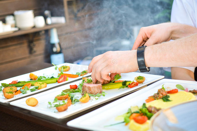 Feg filé med grönsaker och kockhänder royaltyfri fotografi