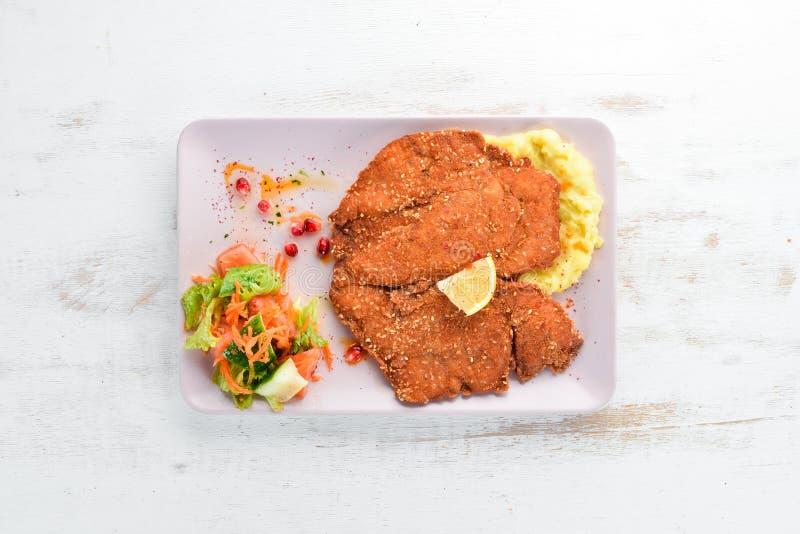 Feg schnitzel med mosade potatisar på en platta P? en tr?bakgrund arkivfoto