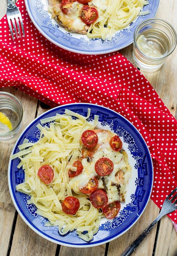 Fega bröst med körsbärsröda tomater, mozzarellaen och pasta royaltyfri bild