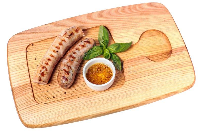 Fega hemlagade grillade korvar med senap och basilika på träplattan Top beskådar Isolerat på vit arkivfoto