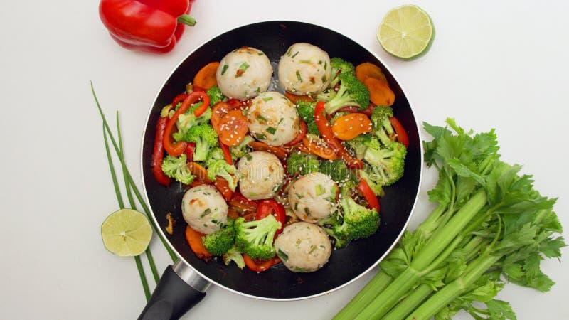Fega köttbullar med grönsaker i en stekpanna royaltyfria foton