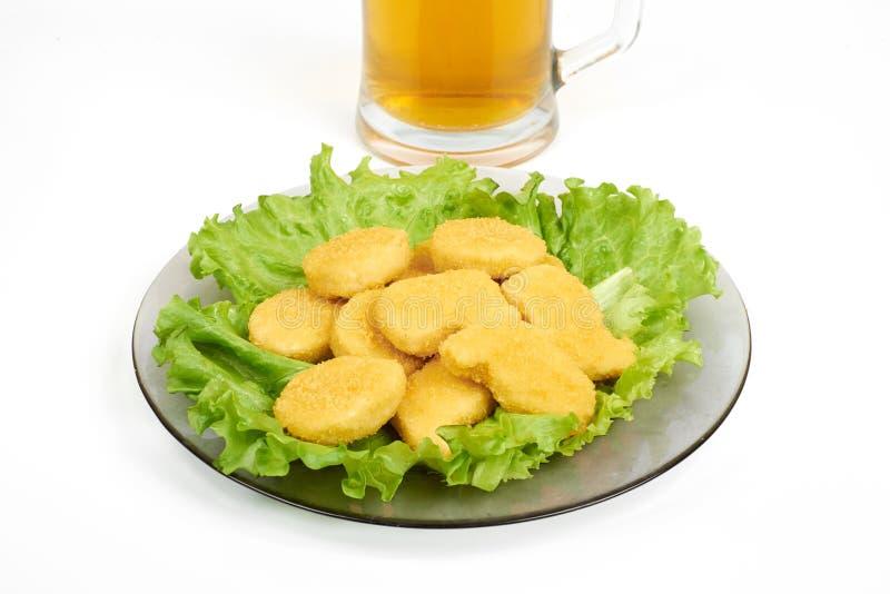 Fega klumpar, grönsaker på en vit platta och öl som isoleras på vit royaltyfri foto