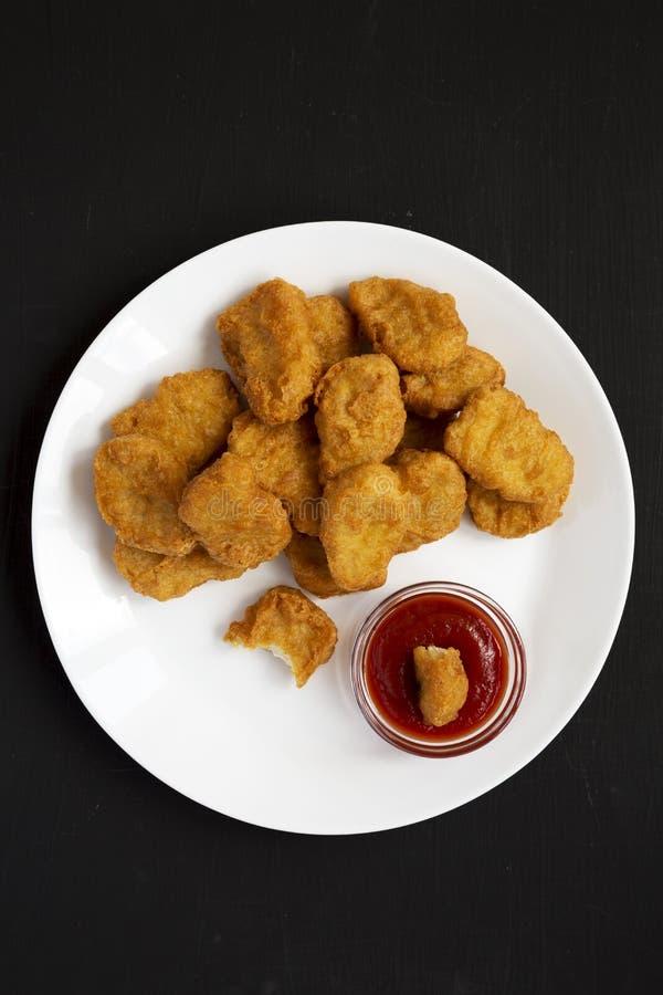 Fega klumpar med ketchup på en vit platta på en svart tabell, bästa sikt L?genhet som ?r lekmanna-, fr?n ?ver, ?ver huvudet arkivbilder