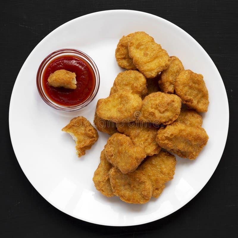 Fega klumpar med ketchup på en vit platta på en svart yttersida, över huvudet sikt L?genhet som ?r lekmanna-, fr?n ?ver, b?sta si royaltyfria foton