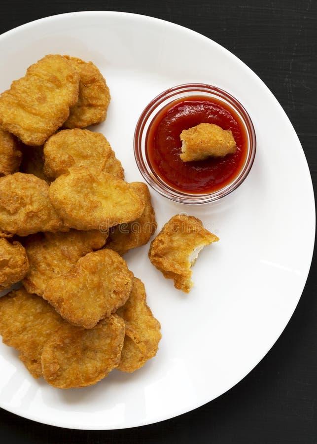 Fega klumpar med ketchup på en vit platta på en svart yttersida, bästa sikt Lekmanna- l?genhet, ?ver huvudet, fr?n ?ver N?rbild royaltyfria bilder