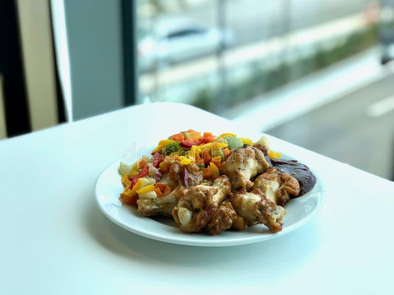 Fega vingar med grillfestsås och grönsaker som är klara att tjäna som med plattan på restaurangen arkivfoton