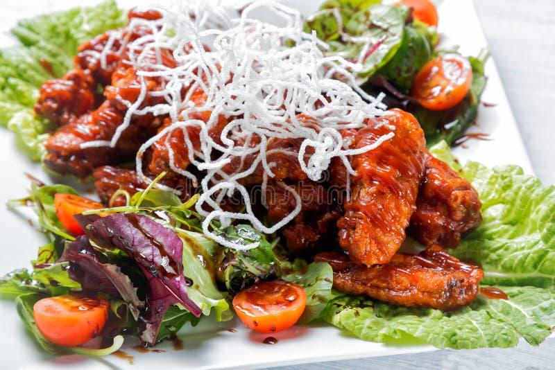 Fega vingar med grillfestsås, sallad, tomater och chiper på den vita plattan Slut upp med den selektiva fokusen arkivfoto