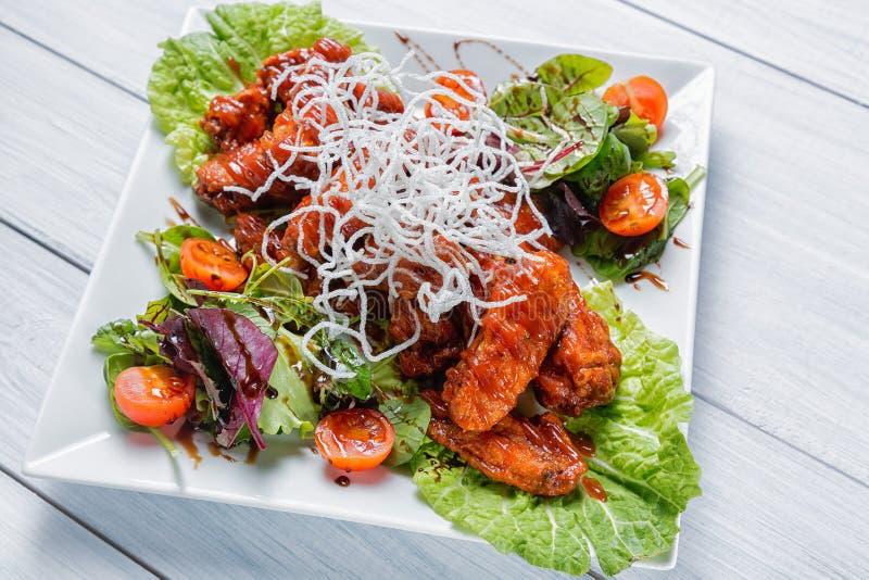 Fega vingar med grillfestsås, sallad, tomater och chiper på den vita plattan Slut upp med den selektiva fokusen arkivbild
