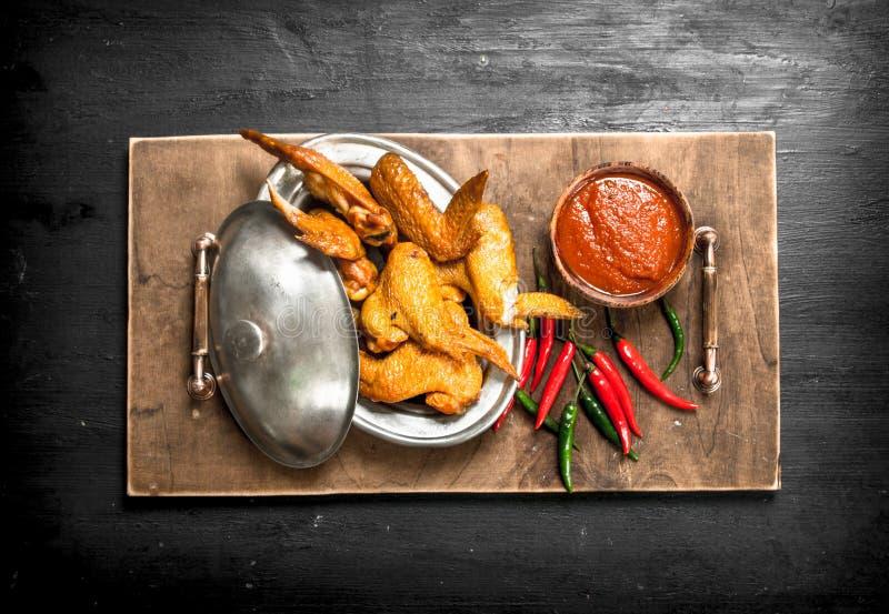 Fega vingar med sås och peppar för varm chili arkivbilder