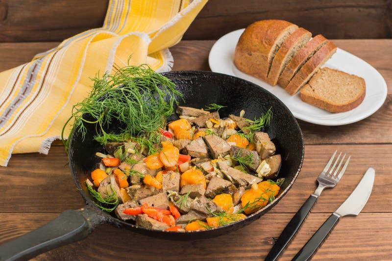 Fegato brasato con le cipolle, le carote, le patate e le spezie sul piatto di pietra Priorità bassa di legno Primo piano fotografie stock libere da diritti