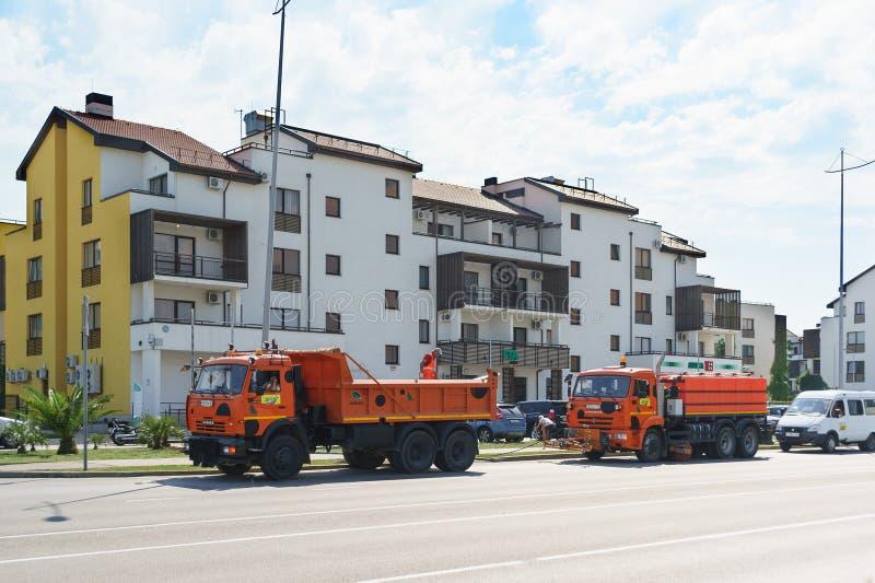 Fegen Sie und reparieren Sie Ausrüstung Straßenreparatur und Baumanagement nahe niedrigen Wohngebäuden stockfotografie