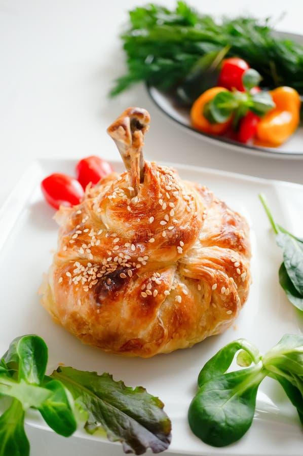 Fegt ben i degen med potatisar, tomater, lökar och kryddor som bakas i ugnen royaltyfria bilder
