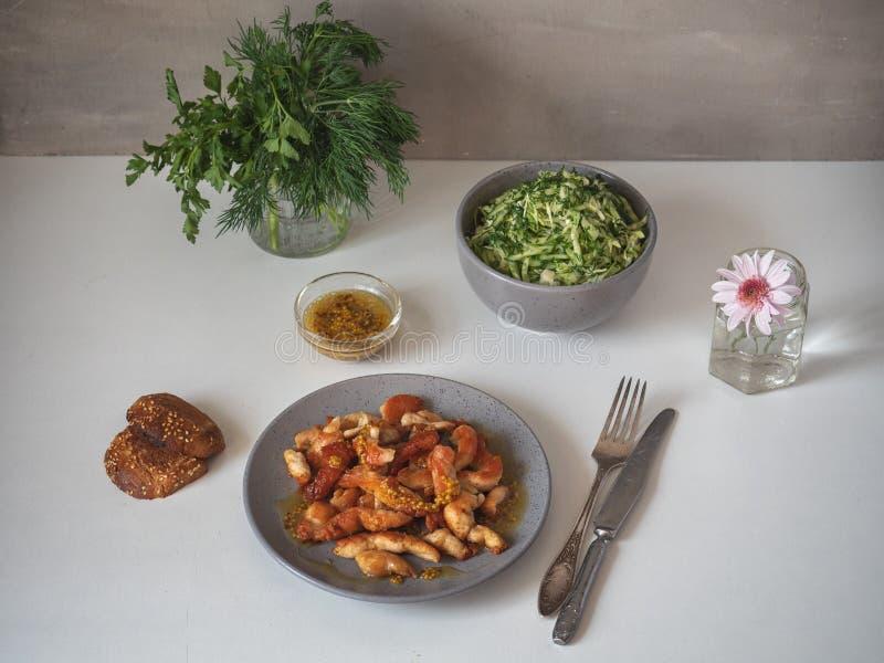 Fegt bröst för stek på en grå platta, sallad från ny kål och gurkan med smaktillsats från nya örter i ett djupt arkivbild