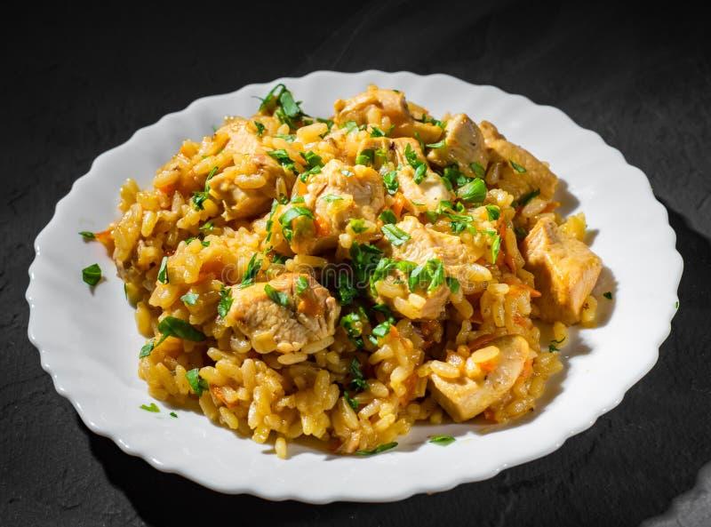 Fegt bröst med ris och grönsaker i den vita plattan på mörker arkivfoto