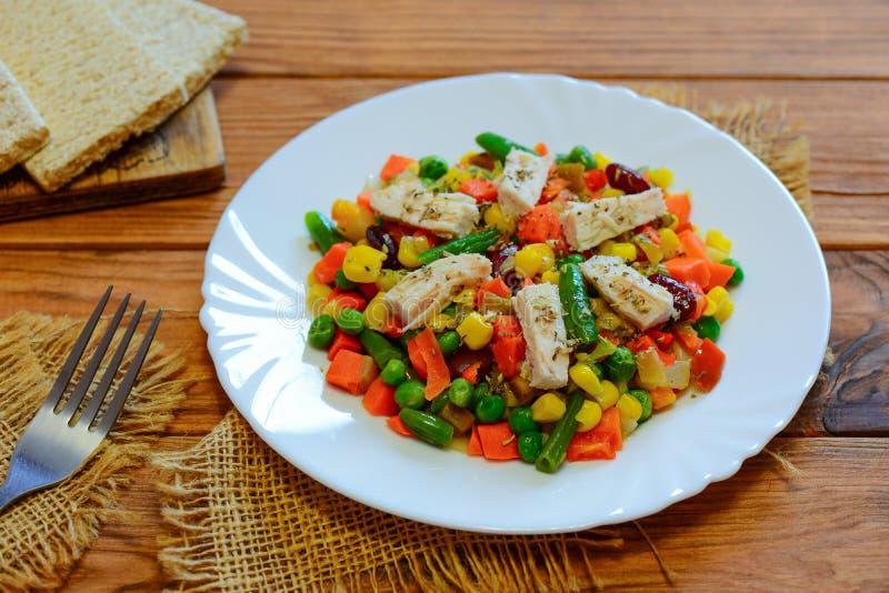 Fegt bröst och blandad grönsakragu på portionplattan och trätabellen Låg-kalori feg grönsakragu arkivfoto