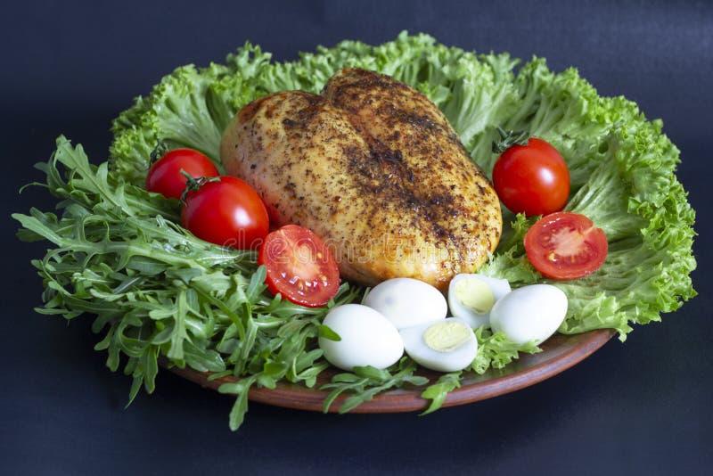 fegt bröst på grönsallatsidor med tomater och vaktelägg royaltyfri bild