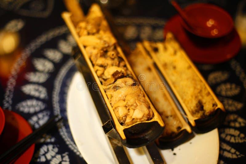 Fegt och ris som lagas mat i det tjocka bamburöret som är declicious arkivfoto