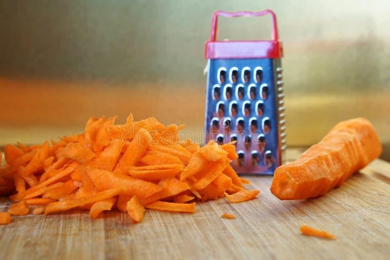 Fehlanpassung: eine kleine Reibe und eine große Karotte sind auf dem Schneidebrett stockfoto