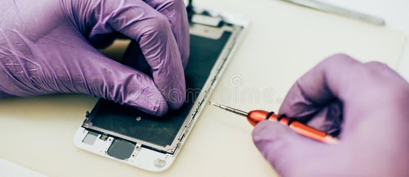 Fehlerhafter Handy der Technikerreparatur in elektronischem Smartphone t lizenzfreie stockfotos