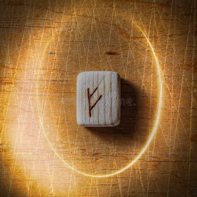 Fehu Handgjorda scandinavian tr?runor p? en tr?tappningbakgrund i en cirkel av ljus begrepp av f?rm?genhet royaltyfri bild