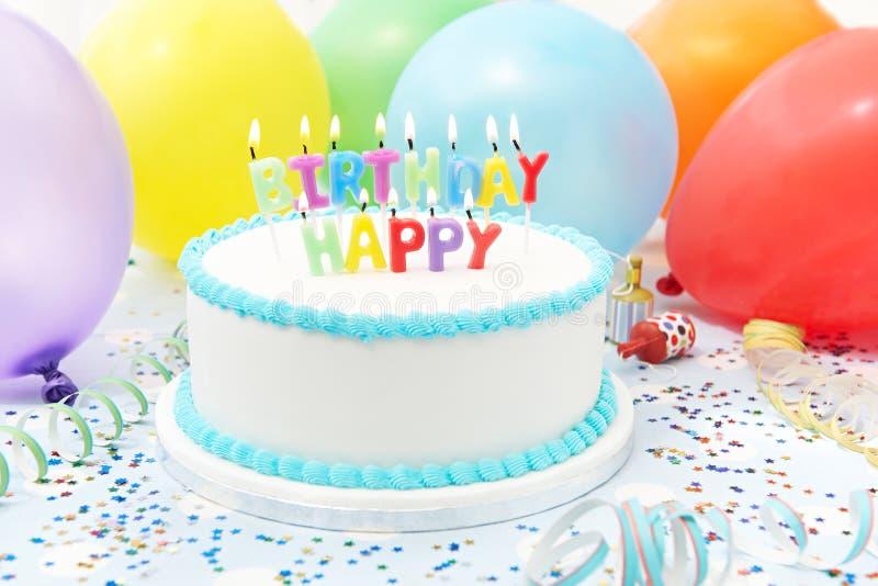 Feier-Kuchen mit den Kerzen alles Gute zum Geburtstag buchstabierend lizenzfreie stockfotografie