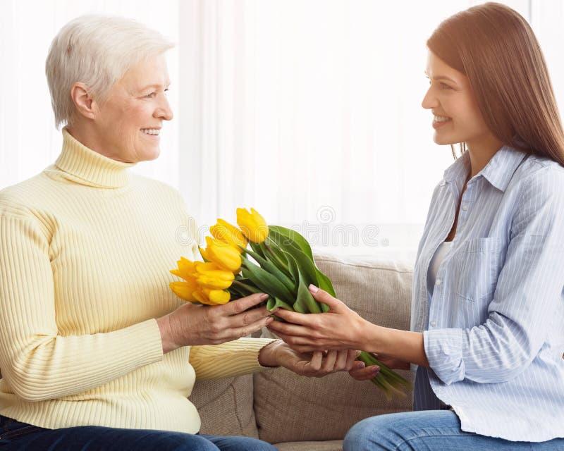 Feiern Mutter ` s von Tag Tochter, die Blumenstrau? gibt, um zu bemuttern stockbild
