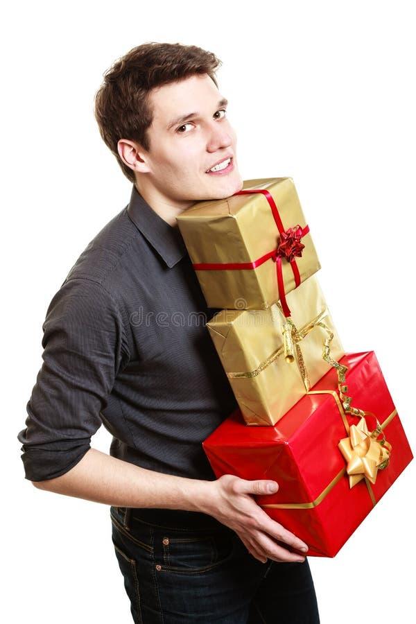 Feiertag. Junger Mann, der Geschenkgeschenkkästen gibt stockfotos