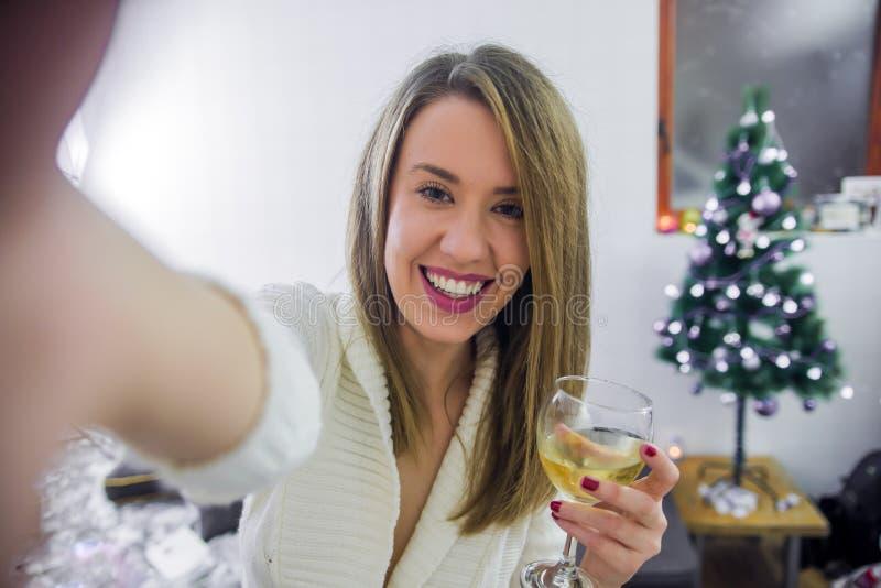 Feiertage, Winter und Leutekonzept - glückliche junge Frau, die zu Hause selfie über Weihnachtsbaum nimmt lizenzfreie stockbilder