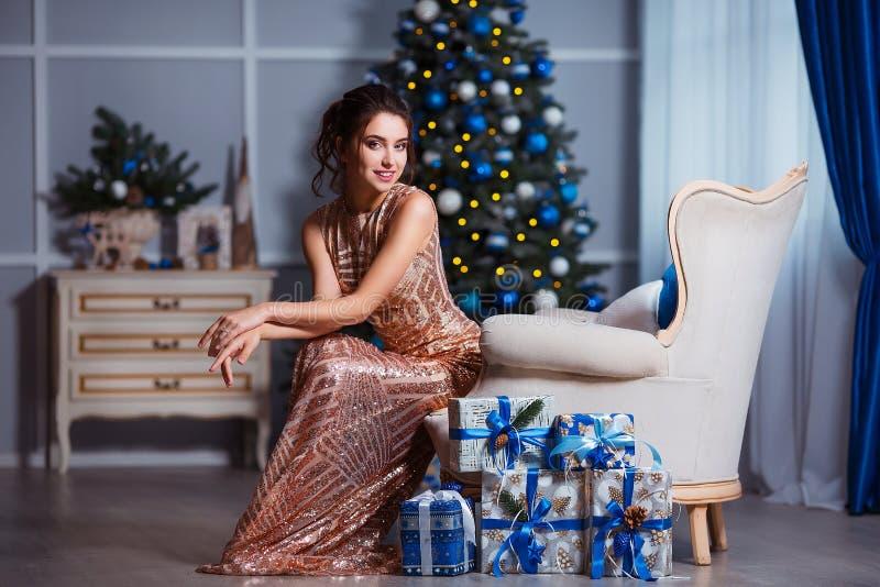 Feiertags-, Feier- und Leutekonzept - junge Frau im eleganten Kleid über Weihnachtsinnenraumhintergrund stockbild