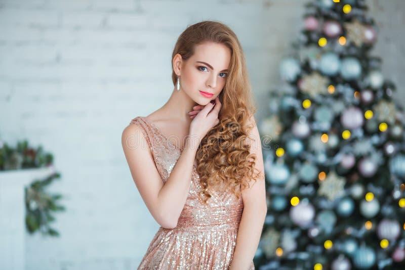Feiertags-, Feier- und Leutekonzept - junge Frau im eleganten Kleid über Weihnachtsinnenraumhintergrund lizenzfreies stockfoto