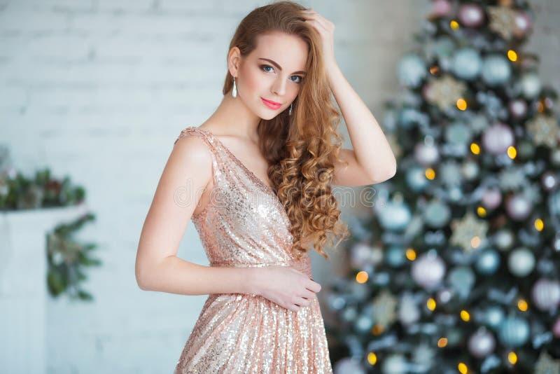Feiertags-, Feier- und Leutekonzept - junge Frau im eleganten Kleid über Weihnachtsinnenraumhintergrund lizenzfreie stockfotos