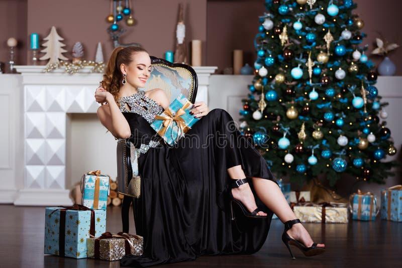 Feiertags-, Feier- und Leutekonzept - junge Frau im eleganten Kleid über Weihnachtsinnenraumhintergrund lizenzfreie stockbilder